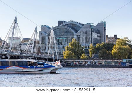 LONDON, UK - OCTOBER 1, 2015: Office building on Charing Cross station with bridge and Thames Clipper boat on river in London, England