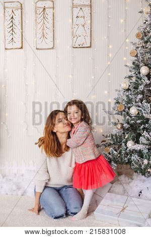 Family moments on Christmas eve, happy mother and daughter. Lovely moment with presents, lights  and decorated tree on backgrounds.