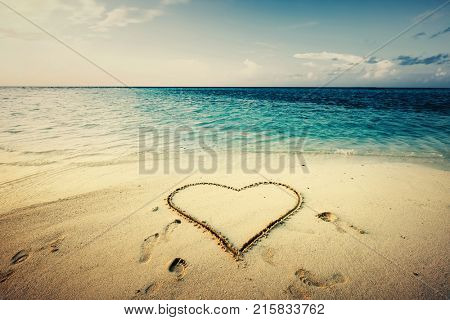 Heart shape drawn on a sand at the seaside. Love symbol. Tropical view.