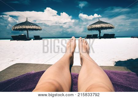 Woman's legs laying on a sunbed, a view of a beach and few resting spots. First person view. Maldives vacation