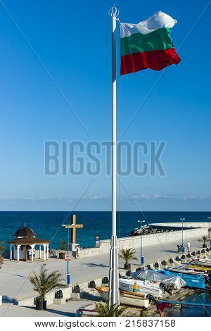 POMORIE BULGARIA - AUGUST 26 2017: Chapel of St. Nicholas in the sea port of the seaside resort town of Pomorie and the national flag of Bulgaria in the foreground.