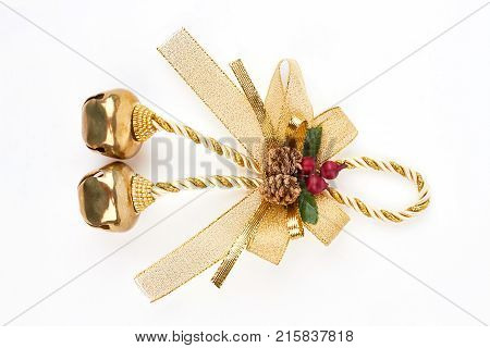 Golden bow with jingle bells. Golden jingle bells on a rope with a bow isolated on a white background. Shiny golden Christmas bells decorations.