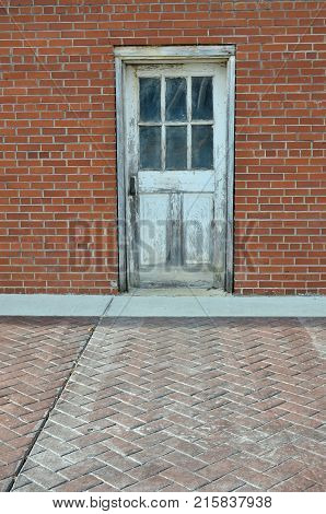 Old wooden door with white paint fading on red brick wall