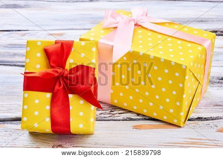 Two yellow gift boxes, wooden background. Gift boxes wrapped in yellow dotted tissue paper and tied with satin ribbon. Beautiful Christmas gifts.