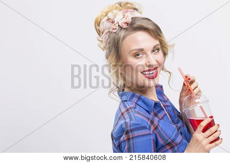 Youth Fashion and Lifestyle Concepts. Alluring and Happy Caucasian Blond Girl Posing in Checked Shirt and Headband Drinking Juice Using Straw.Horizontal Image Orientation