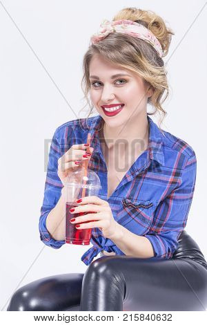 Youth Lifestyle Concepts. Portrait of Happy Smiling Caucasian Blond Woman in latex pants Posing with Cup of Red Juice and Straw. Against White.Vertical Image Composition
