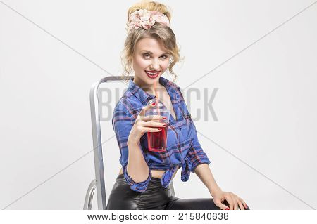 Youth Lifestyle Concepts. Portrait of Happy Smiling Caucasian Blond Woman in Black Latex Pants Posing On Ladder with Cup of Red Juice and Straw. Against White Background.Horizontal Image