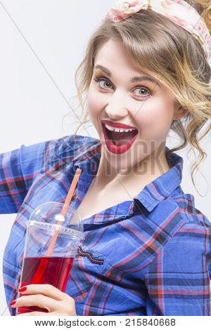 Youth Lifestyle Concepts. Extremely Surprised Caucasian Blond Woman in Checked Shirt Drinking Red Juice Using Straw. Posing On White.Vertical Image