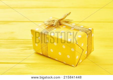 Yellow gift box on yellow background. Yellow dotted gift box tied with golden ribbon on yellow wooden background. Beautiful Christmas and New Year present.