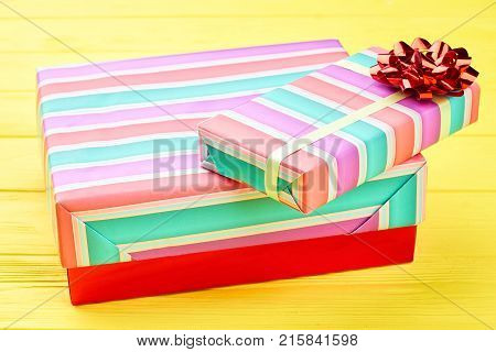 Christmas gift boxes and red bow. Big and small colorful boxes with presents on yellow wooden background. New Year and Christmas concept.