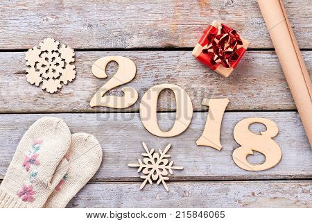 New Year 2018 handmade decoration on wood. Carved wooden number 2018, handmade wooden snowflakes, little gift box, craft paper and pair of mittens, retro wooden background. Happy New Year 2018.