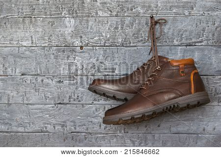 Brown stylish men's boots hanging on a nail on the wall vintage background. The background of a wooden wall and men's shoes.