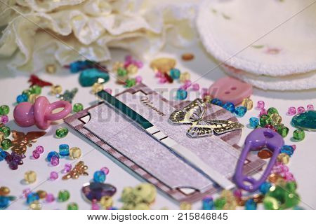 Positive pregnancy test in scrap book frame with butterfly,  cute baby accessories and spilled colored  seed beads around.