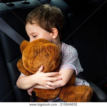 Boy hugging teddy bear in the car