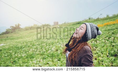 Asian women relax in the holiday. Stand in the cold winter garden. Mountain Park happily. In thailand