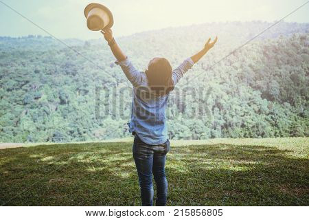 Asian man travel relax in the holiday. Standing hand in the park on the lawn. Mountain Park happily. In Thailand