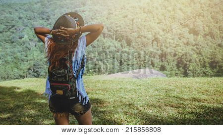 Asian women travel relax in the holiday. Standing hand in the park on the lawn. Mountain Park happily. In Thailand