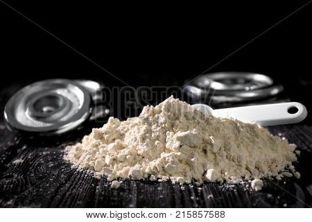 Heap of protein powder with scoop on table, closeup