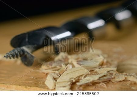 Shavings and wood drill bit on wooden board as woodworking background image. Selective focus