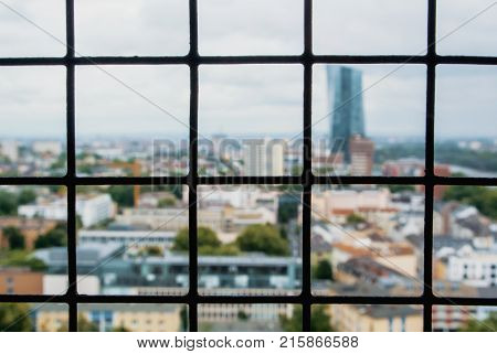 Blurred Areal View To Panorama Of Frankfurt City Center Through A Metal Protective Grid Cage Net At