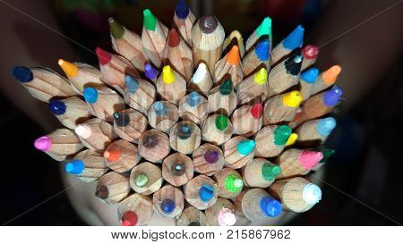 Many colored pencils in hands / Wooden colored pencils / Background of colored pencils