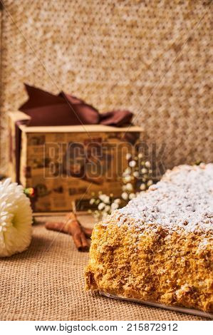 Homemade Napoleon cake. Layered puff pastry napoleon cake with powdered sugar and butterscotch frosting on sackcloth decoration background. Sweet dessert food
