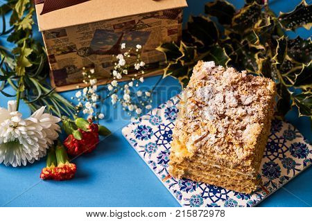 Piece of Cake Napoleon with sour cream. Layered puff pastry napoleon cake with powdered sugar and butterscotch frosting on blue decoration background. Sweet dessert food