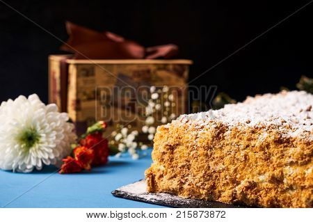 Delicious Napoleon cake with with sour cream. Layered puff pastry napoleon cake with powdered sugar and butterscotch frosting on sackcloth decoration background. Sweet dessert food