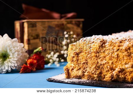 Cake Napoleon with sour cream. Layered puff pastry napoleon cake with powdered sugar and butterscotch frosting on blue decoration background. Sweet dessert food