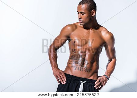 athletic sweaty shirtless african american sportsman standing with hands on waist isolated on grey