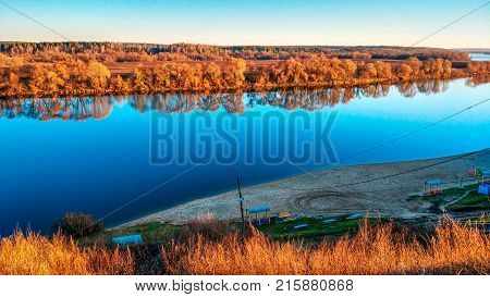 Beautiful scenery of the Oka river in Kolomna, autumn panorama, bright autumn in November. Golden trees, blue sky. Bright reflection of trees in the river. Sandy beach.