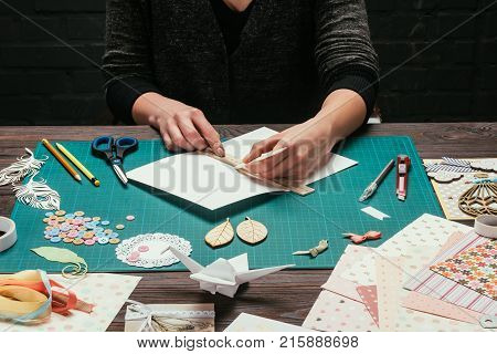 cropped image of designer cutting paper for scrapbooking greeting postcards
