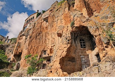 Civita di Bagnoregio, Viterbo, Lazio, Italy: the rock face of the tuff hill where it was built the medieval village with caves and rock-cut cellars