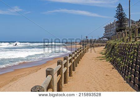 Wooden Pole Barrier On Beachfront Against Coastal  Landscape