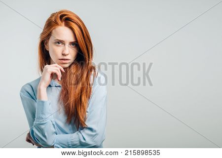 Portrait of young annoyed female with freckles and pursed lips having disappointed unhappy look, frowning and pouting