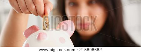 A young smiling chinese woman holding bitcoin coin in his hand thrusts it into piggy bank form of pink piggy saving storage theme in crypto currency.
