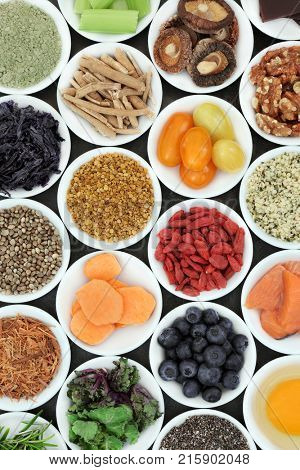Berry fruit, vegetables, fish, nuts, seeds and herbs for brain boosting super foods. Healthy food concept with super foods high in omega 3, vitamins, minerals, antioxidants and anthocyanins. Top view.