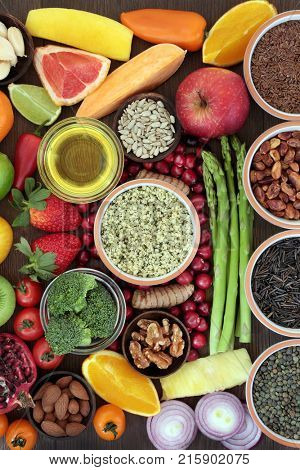 Health and super food concept to promote fitness and a healthy heart with fruit, vegetables, nuts, seeds, grains an pulses. Foods high in omega 3, antioxidants, vitamins and smart carbohydrates.