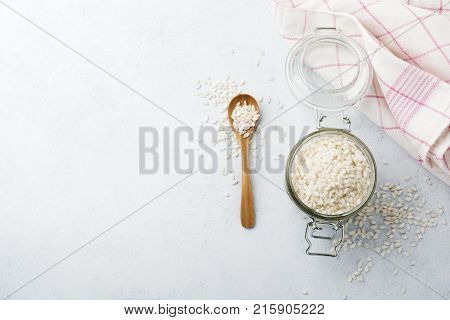 Raw White rice variety Arborio for Italian risotto dishes in glass jar on white concrete or stone background. Selective focus. Top view. Copy space.