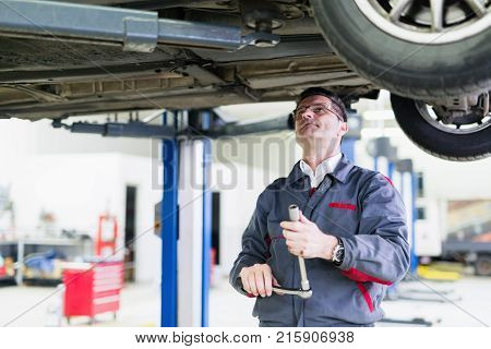 Handsome car mechanic working at automotive service center