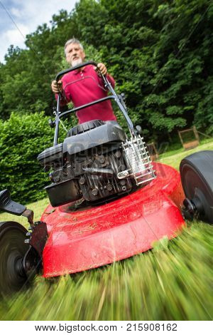 Senior man mowing the lawn in his garden (selective focus; shallow DOF) - motion bl