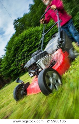 Senior man mowing the lawn in his garden (motion blurred image)