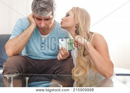 Blonde gold digger wife asking 100 Euro from sad husband indoors