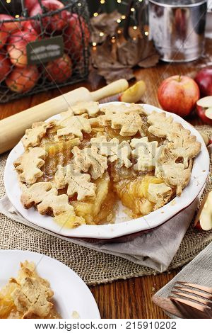 Freshly baked apple pie with top crust cut into autumn leaves shape and piece missing. Apples in background.