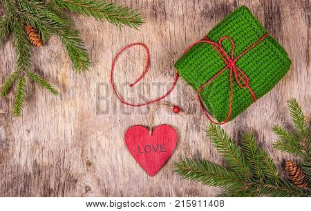 Christmas background with fir tree and knitted gift. Preparing for Christmas. Red heart pendant.