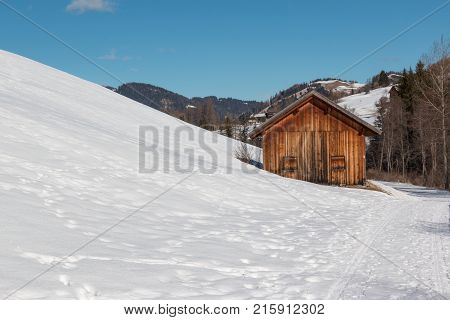 Small Wooden Shack Among Trees In Winter Day With Fresh Snow In The Mountains, Winter Landscape