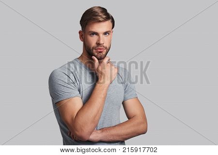 Irresistible man. Charming young man keeping hand on chin and looking at camera while standing against grey background