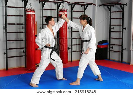 Young man and woman practicing martial arts in dojo