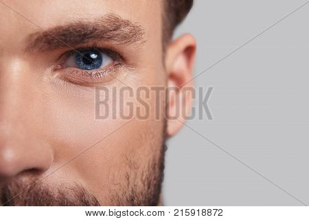 Looking deeply into your heart. Close up of good looking young man half face looking at camera while standing against grey background