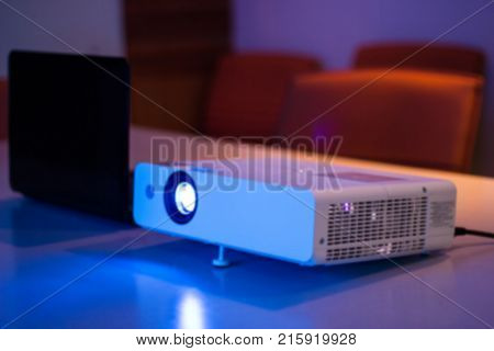 projector connected to Laptop on for presentation in a meeting room with notebook background